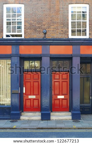 Red doors on building Exterior of modern building with two red doors, street in foreground. - stock photo