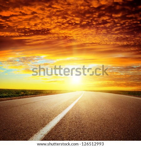 red dramatic sunset over asphalt road - stock photo