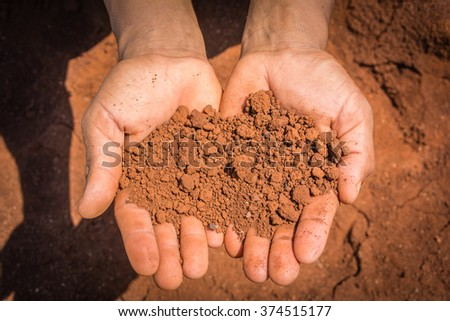 Red dry soil on hands in the drought land. - stock photo