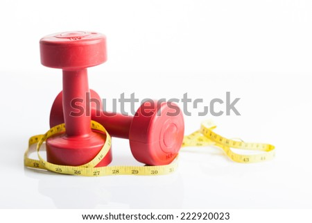Red dumbbells weight with measuring tape for diet concept on white background - stock photo