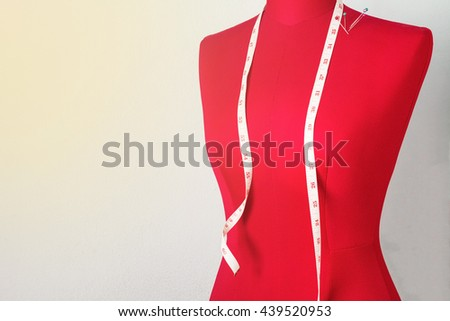 Red dummy with measuring tape in tailors studio - stock photo