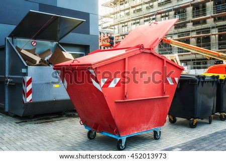 Red dumpster, recycle, waste and garbage bins near new office building. Construction site on background - stock photo