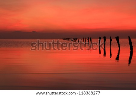 Red dusk sky with old fence posts at the Great Salt Lake, Utah, USA. - stock photo