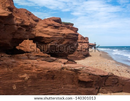 Red earth cliffs and arches along the eroding shoreline of Prince Edward Island, Canada - stock photo