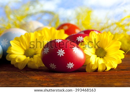 Red Easter eggs and yellow flowers on nature background  - stock photo