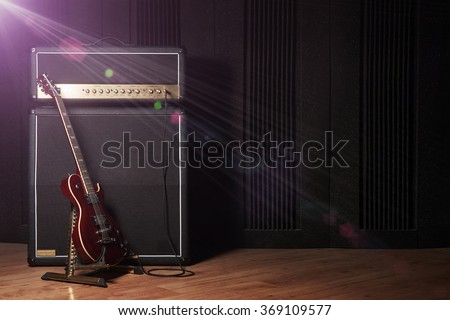Red electric guitar and classic amplifier on a dark background with lens flare effect                               - stock photo