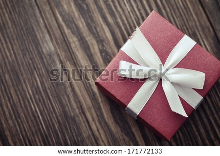 Red elegant gift box on a wooden background - stock photo