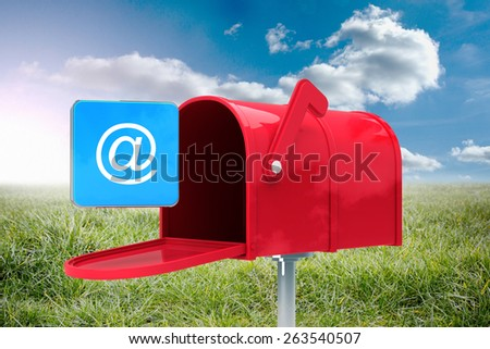 Red email postbox against sunny landscape - stock photo
