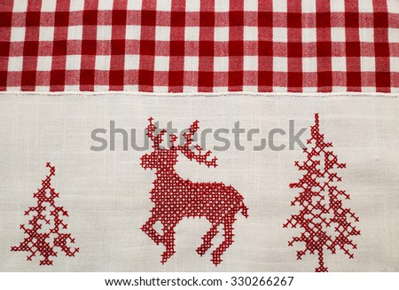 Red embroidered deer, two Christmas tree  on white and checkered plaid linen fabric  tablecloth  background - stock photo