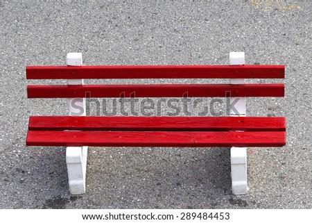 Red empty bench on pedestrian sidewalk - stock photo