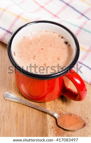 red enamel mug with cold milk and cocoa - stock photo