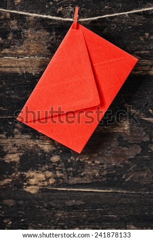 Red  envelop  hanging on the clothesline. On old wood background - stock photo