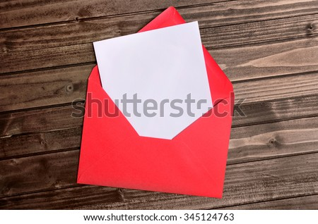 Red envelope with empty paper on wooden table - stock photo