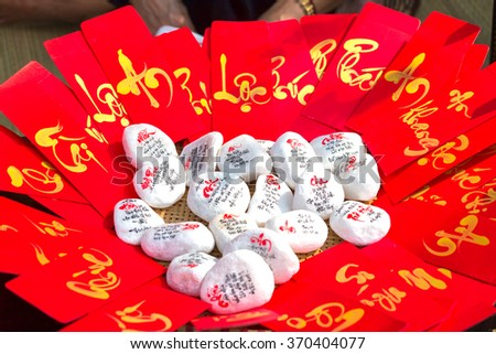 "Red envelopes with text ""property, fortune, happy new year"" in Vietnamese next to the write calligraphy is also for sale in the first day was beautiful and meaningful - stock photo"