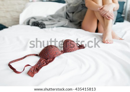 Red erotic brasserie on white bed with girl on it. Red bra on foreground, sexy naked girl with crossed legs on background. Some free space - stock photo