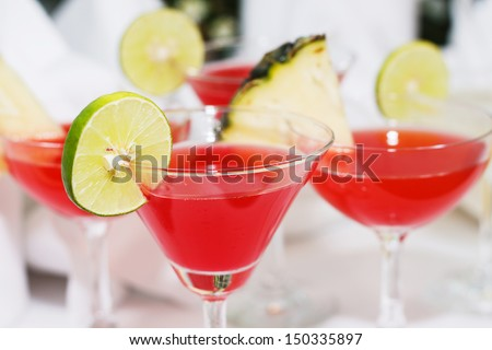 Red exotic cocktails and fruit show on table - stock photo