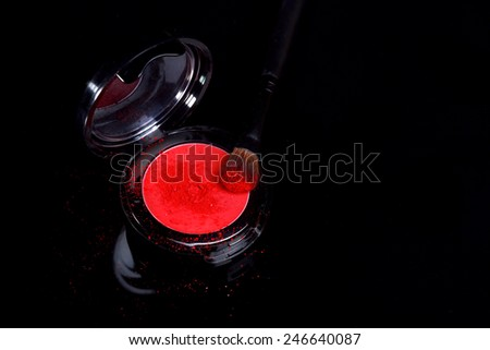 Red Eyeshadow With Brush and Loose Powder on Black Background - stock photo
