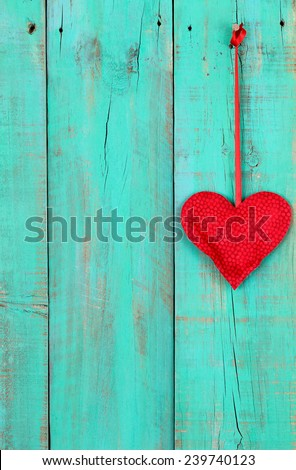Red fabric heart hanging by red ribbon on antique teal blue wooden background - stock photo