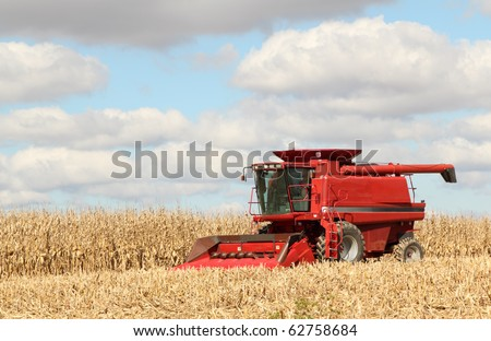 Red farm combine harvesting corn against a blue sky with clouds - stock photo