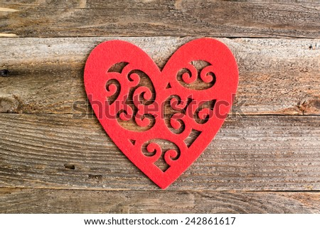 Red felt floral heart on reclaimed wood, valentines day background. - stock photo
