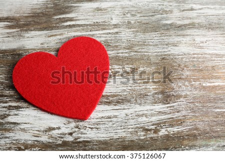 Red felt heart on grey wooden background - stock photo