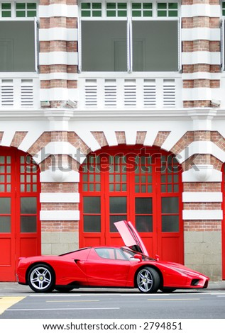 Red Ferrari Enzo in front of Fire Station Singapore - stock photo