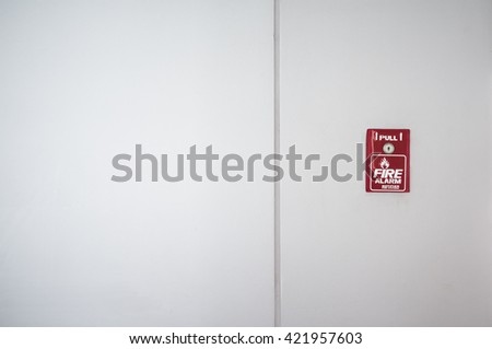 Red fire alarm box on old white wall for security system - stock photo