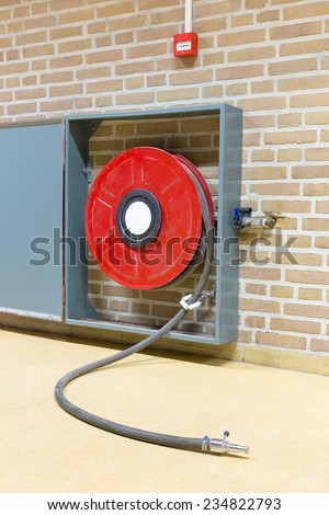 Red fire hose on reel at wall - stock photo