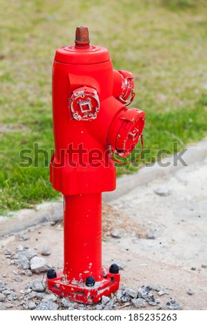 Red fire hydrant stands on the roadside with green grass on a background - stock photo