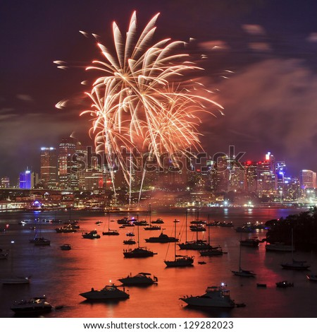 Red Fire palm tree during firework in Sydney new year eve event celebration bright pyrotechnic lights reflect in harbor water over city CBD - stock photo