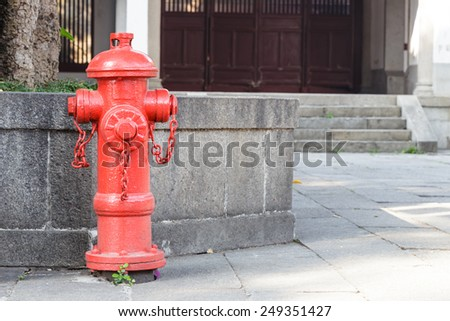 Red fireplug standing on footpath for fire fighting - stock photo