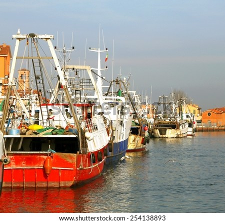 red fishing vessel other ships moored in the harbor - stock photo