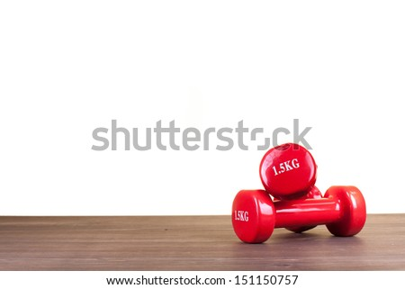 Red fitness dumbbells on wood floor in front of white background - stock photo