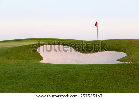 Red flag of golf hole above sand trap or bunker on beautiful course at sunset - stock photo
