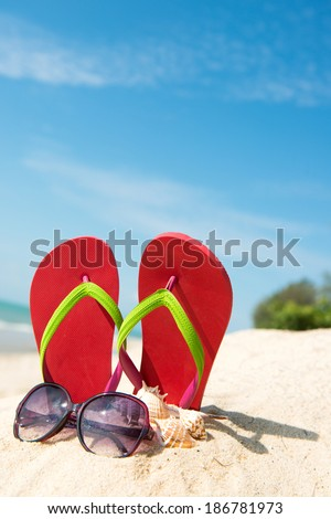 Red flip flop and sunglasses on beach against clear blue sky - stock photo