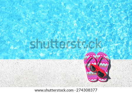 Red flip flops and sunglasses beside blue pool - stock photo