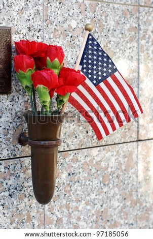 Red flowers and a small American flag at cemetery crypt. - stock photo