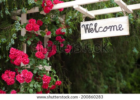 Red flowers and welcome wood panel at hotel entrance - stock photo