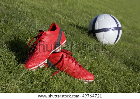 Red football shoes and a ball on the grass - stock photo