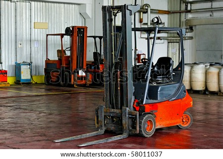 Red forklift parked in modern factory warehouse - stock photo