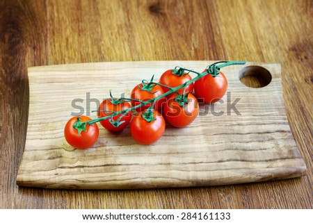 Red fresh cherry tomatoes on the wood table - stock photo