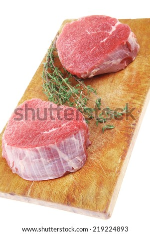 red fresh fillet chops : two raw beef fillet chops on wooden board with small thyme twig ready to prepare . isolated over white background - stock photo