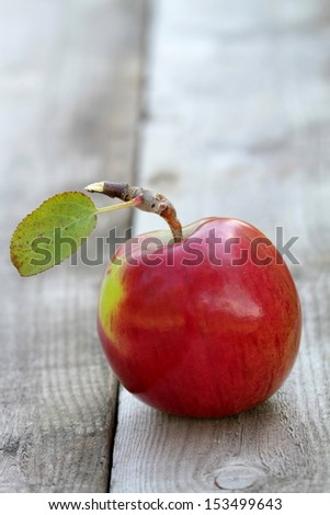 Red fresh organic apple on gray old wooden table - stock photo