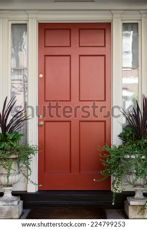 Red Front Door with Surrounding White Door Frame and Windows and Greenery - stock photo