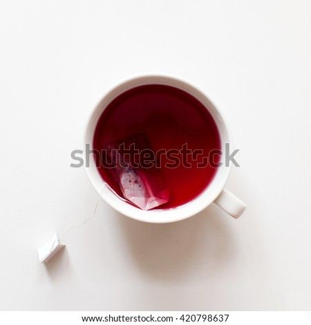 Red fruit tea cup with tea bag, top view on white background with copy space. Healthy tea drinking. - stock photo