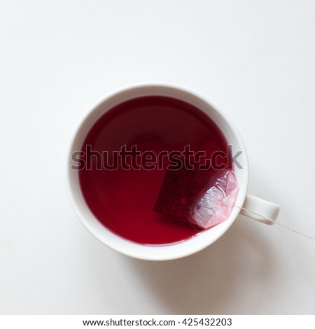 Red fruit tea with tea bag, top view with copy space. Healthy tea drinking. - stock photo