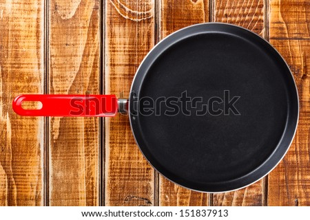 Red frying pan on wooden board - stock photo