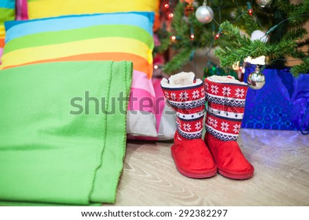 Red fur boots standing under green tree near color pillows and blanket, Christmas Eve - stock photo