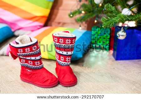 Red fur boots with Christmas decor standing under green tree - stock photo