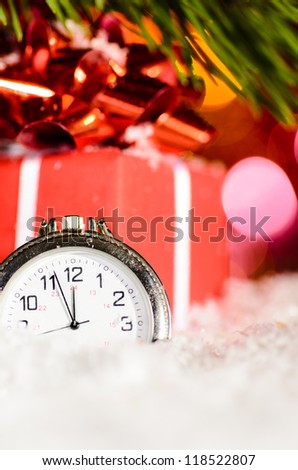 red gift box and clock on snow with christmas tree branch on blurred background - stock photo